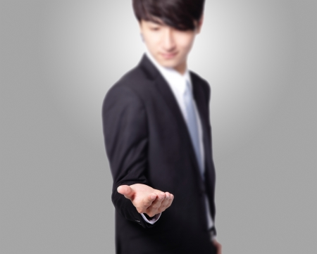 open palm: handsome Business man with empty hand on gray background, great for you design, asian model Stock Photo