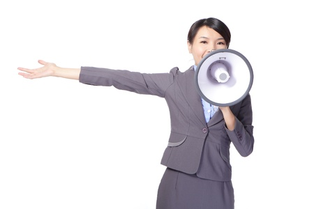 Business woman with megaphone yelling and showing something with open palm isolated on white background, asian model photo