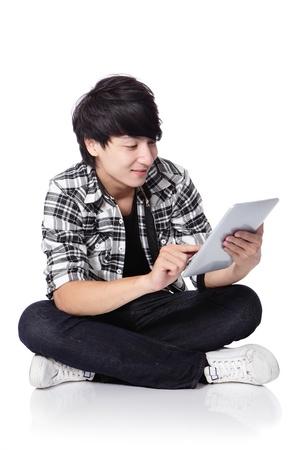 handsome student: Joven estudiante guapo feliz usando la computadora Tablet PC y se sientan en el suelo en toda su longitud sobre fondo blanco, hombre asi�tico Foto de archivo
