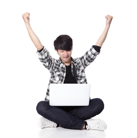 Young student Man with laptop and sitting on floor and excited raise his arms in full length isolated on white background, asian model photo