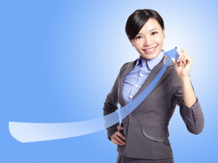 success business woman draw arrow with blue background, asian model photo