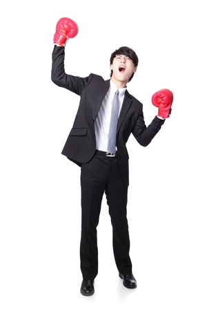 beat the competition: young handsome Businessman wearing boxing gloves in a victory pose and raise his arms in full length isolated on white background, asian model
