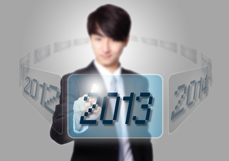 Enter 2013 new year - Business man pressing touch screen button with 2013 number on gray background, asian model photo