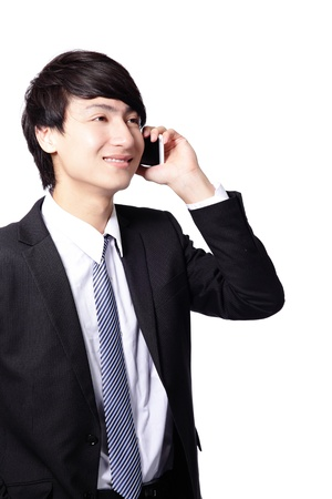 Portrait of handsome young business man using cell phone, smiling, isolated on white background, model is a asian male photo