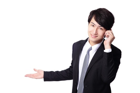 please call this number, handsome young business man showing something by hand and using mobile phone isolated on white background, model is a asian male Stock Photo - 17166134