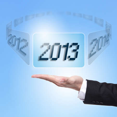 hand of Business man holding screen button with 2013 number, happy new year 2013 in business concept photo