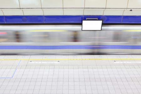 platform at a metro railway station with motion blur speed train and blank tv billboard photo