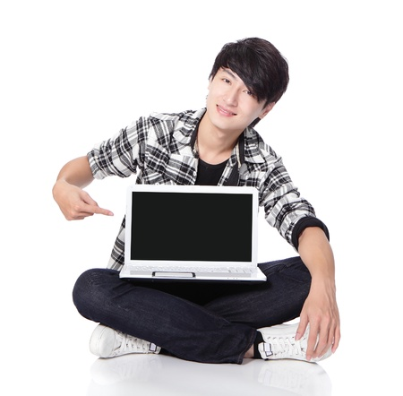 he: Young man using a laptop and sitting on floor, he finger point to empty computer screen