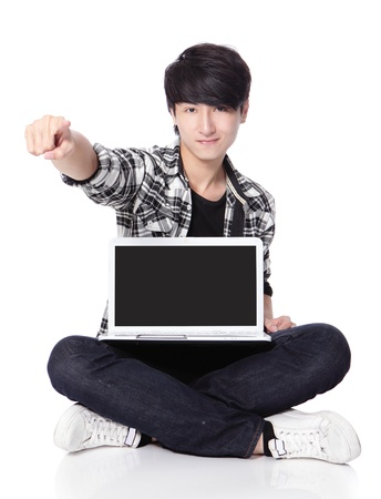 Young man using a laptop (empty computer screen) and sitting on floor photo