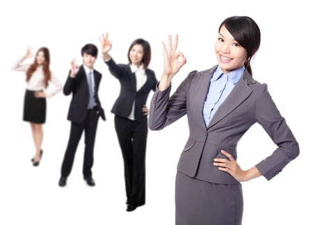 ok sign: Perfect - business woman making the ok sign with her team behind Stock Photo