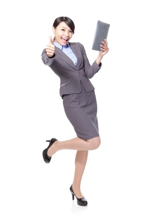 Young beautiful business woman happy using tablet pc and show thumb up in full length isolated on white background photo