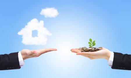 property insurance: Manos de negocios con el dinero y la casa de las nubes en el fondo azul cielo, concepto por concepto de familia Bienes y