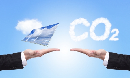 eco concept - choice solar panel or co2, Business man hold Alternative Energy (solar cell ) with blue sky and cloud background photo