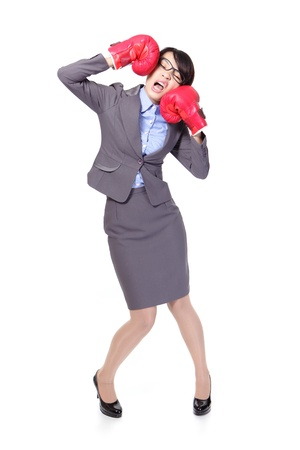 defeated: Funny businesswoman wearing boxing gloves and knock down itself, defeated loser woman - business concept - hopeless. Young Asian female model isolated on white background.