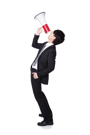 Young business man shouting into a megaphone in full length isolated over a white background, profile side view, asian model photo