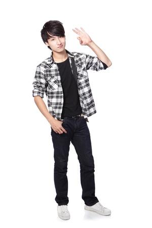 Casual jonge man in volledige lichaam te tonen ok handgebaar geïsoleerd op witte achtergrond, Aziatische model Stockfoto