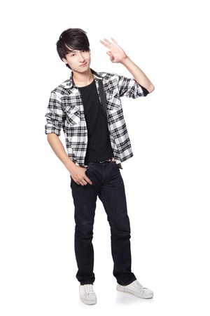 Casual young man in full body show ok hand gesture isolated on white background, asian model photo