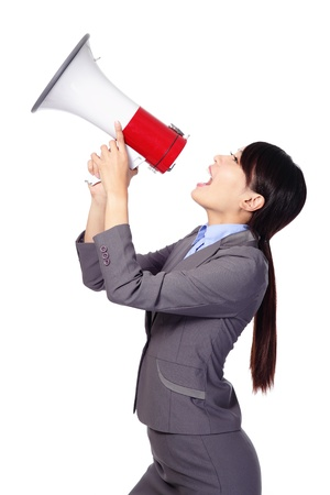 Business woman screaming loudly in a megaphone (face in profile) isolated on white background, model is a asian beauty photo