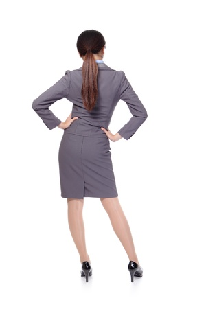 backview: Business woman from the back - looking at something isolated over a white background, asian model Stock Photo