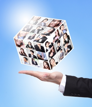 Human Resources concept: business man hand holding a magic cube made by all business people face photo