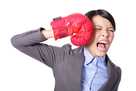 Funny businesswoman wearing boxing gloves and knock down itself, defeated loser woman - business concept - hopeless. Young Asian female model isolated on white background. photo