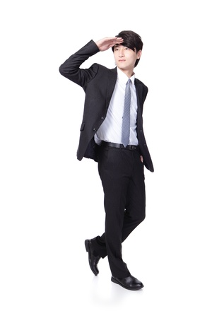 Successful handsome business man purposefully looking away to empty copy space in full length isolated on white background, mode is a asian male photo