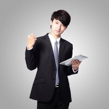 Business man happy using tablet pc isolated on gray background, asian model photo