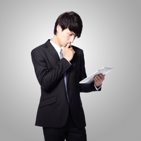 intrigued: young business man is intrigued by the news and reading on his new tablet pad isolated on gray background, asian model Stock Photo