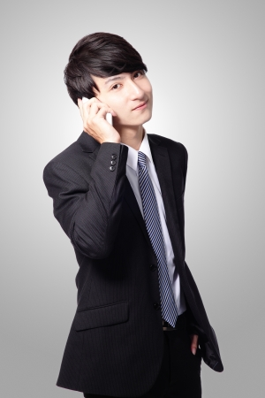 Portrait of handsome young business man using cell phone, smiling isolated on gray background, asian model photo