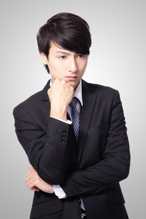 Portrait of a young business man looking depressed from work isolated over gray background, asian model photo