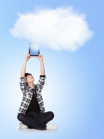 Young man holding tablet pc with cloud computing background, asian model photo