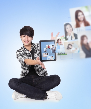 Young man using social networking with friends. Portrait of handsome guy using his tablet pc looking at camera and smiling. blue background, asian model photo