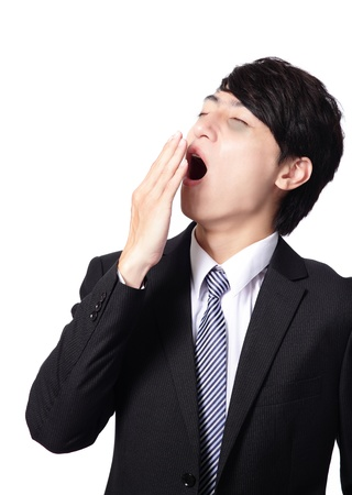 overworked business man yawning with black rim of eye, face in profile,  isolated on white background, model is a asian people photo