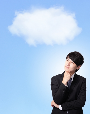 blue sky thinking: portrait of a business man thinking against a cloudy sky background, asian model