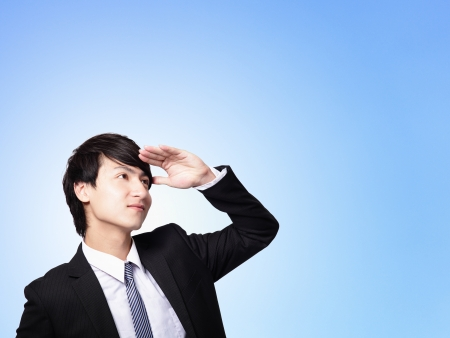 Successful handsome business man purposefully looking away to empty copy space isolated on blue background, mode is a asian male Stock Photo - 17495768