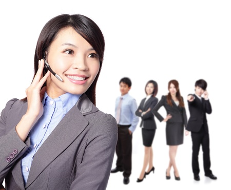 Smiling pretty business woman with headset. Smiling call center executive with colleagues in blur background isolated on white background, asian model Stock Photo - 17495769