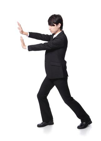 hombre empujando: joven hombre de negocios empujando algo en todo el cuerpo aislado en el fondo blanco, asi�tico modelo masculino