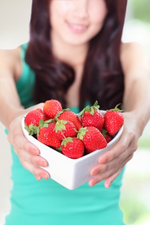 Strawberry - beautiful woman showing fresh strawberries with nature green background, focus on fruit, asian beauty mode  photo