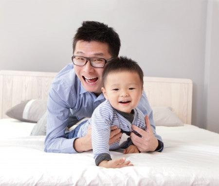 bedsheet: young father play with his son boy on the bed at home, asian lifestyle