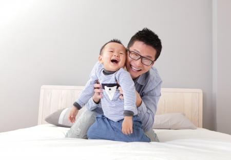padre e hijo: joven padre jugando con su hijo joven en la cama en su casa, estilo de vida asi�tico