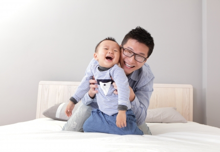 father and son: young father play with his son boy on the bed at home, asian lifestyle