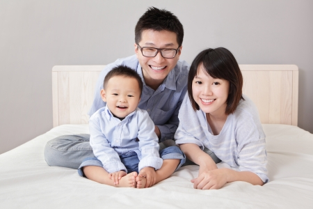 family asia: A happy family lying on white bed in the bedroom with gray wall for copy space, asian people