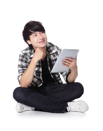 young student man happy using tablet pc and look to copy space and sitting on floor in full length isolated on white background, asian Stock Photo - 17591996