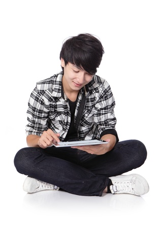 arise: young student man happy using tablet pc and sitting on floor in full length isolated on white background, asian people Stock Photo