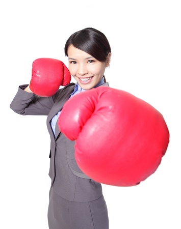fist fight: Portrait of beautiful young business woman wearing boxing gloves punching isolated on white background, asian model