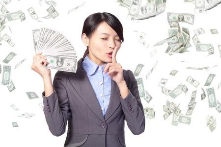 happy rich woman: donna d'affari dito sulle labbra chiedendo tranquillo con la caduta di denaro isolato su sfondo bianco, modello asiatico Archivio Fotografico