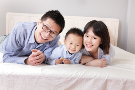 A happy family lying on white bed in the bedroom with gray wall for copy space, asian people photo