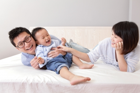 asian baby: happy family playing on white bed in the bedroom at home, asian people