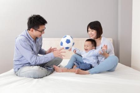 asian home: Famiglia felice che giocano giocattolo calcio sul letto bianco in camera da letto a casa, le persone asiatiche Archivio Fotografico