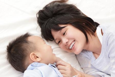 madre e hijo: Madre e hijo sonre�r y mirar el uno al otro y acostado en la cama de color blanco en el dormitorio en la casa, la familia asi�tica